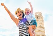 Portrait Of Happy Mother And Baby Girl Rejoicing In Front Of Leaning Tower Of Pisa, Tuscany, Italy