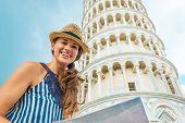 Portrait Of Happy Young Woman With Map In Front Of Leaning Tower Of Pisa, Tuscany, Italy