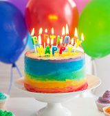 Rainbow Cake And Cupcakes Decorated With Birthday Candles