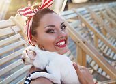 Beautiful Pin Up Girl With Puppy Near The Swimming Pool