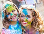 Happy Mother With Little Daughter On Holi Festival