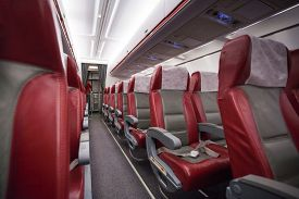 stock photo of transpiration  - Empty saloon of commercial airplane with rows of red generic seats in the aisle - JPG