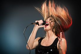 pic of rocking  - A young woman rock singer with tousled long hair holding a microphone with stand and singing with a wide open mouth - JPG