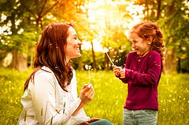 stock photo of dandelion seed  - Mother with small daughter blowing to dandelion  - JPG