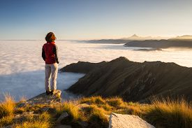 stock photo of italian alps  - Female hiker reaching her goal at the mountain top and looking at majestic panoramic view of the italian western Alps with M - JPG