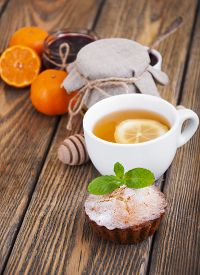image of bakeshop  - A cup of tea with lemon and honey homemade muffins on wooden background - JPG