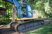 picture of vegetation  - The claw of a frontloader devestates the vegetation growing in a residential neighborhood - JPG