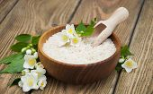 stock photo of jasmine  - Wooden plate with jasmine rice and jasmine flowers on a wooden background - JPG