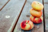 foto of saturn  - Fresh Saturn peaches on old wooden background - JPG