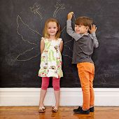 picture of little angel  - Full length portrait of cute little girl standing and little boy drawing angel wings around her on blackboard - JPG