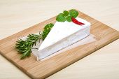 foto of brie cheese  - Soft brie cheese with rosemary thyme on the wood background - JPG