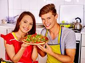 stock photo of guest-house  - Young happy family cooking pizza at kitchen and wating guests - JPG