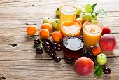 stock photo of fruit-juice  - Glasses of different fruit juices with fruits on a rustic wooden table - JPG