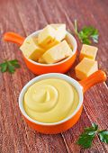 stock photo of shredded cheese  - cheese sauce in bowl and on a table - JPG
