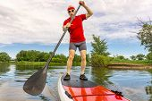 image of collins  - senior muscular male paddler enjoying paddling stand up paddleboard  on a local lake in Fort Collins - JPG