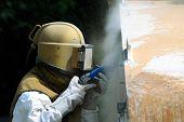 stock photo of sandblasting  - Worker is removing paint by air pressure sand blasting - JPG