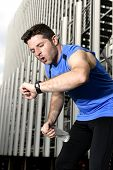 stock photo of fitness man body  - young sport man breathing exhausted after running training on city urban background leaning tired and checking timer watch in fitness and body care concept - JPG