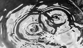 picture of leak  - Water drops from a leaking pipe causing ripples on water surface - JPG