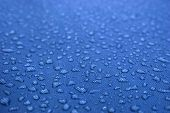 Water drops pattern over a waterproof cloth, blue background
