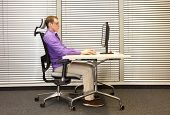 correct sitting position at workstation. man on chair working with computer poster