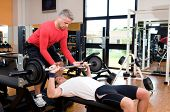 Young man doing weigths on a bench press with the help of the mature instructor at gym
