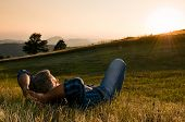 Mature man taking a break and relax in a meadow in the wonderful warm light of the sunset