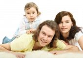 Happy young family - mother and father lie on a white fluffy fur and daughter lie on father poster