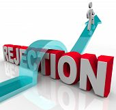 stock photo of rejection  - A person jumps over the word Rejection riding an arrow to success - JPG