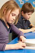 Schoolgirl And Schoolboy Studying In Classroom