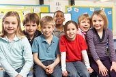 stock photo of school child  - School Children In Classroom Smiling - JPG