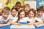 stock photo of 7-year-old  - Schoolchildren In IT Class Using Computer - JPG