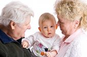 stock photo of nana  - proud grandparents are carrying their cute granddaughter - JPG