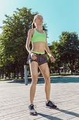 Fit Fitness Woman Doing Stretching Exercises Outdoors At Park. Girl Doing Hamstring Leg Stretching E poster