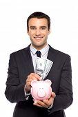 Businessman putting money in piggy bank