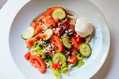 Plate Of Salad With Tomatoes, Cucumber, Bell Pepper, Cream Cheese, Ham On The White Table. Glass Of  poster