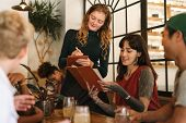 Young Woman With Tattoos Sitting With Friends At A Bistro Table Ordering Giving Her Menu Order To A  poster