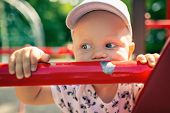 Baby Boy Playing In Playground Alone. Portrait Of Toddler Looking Away With Unhappy Face. Holding A  poster