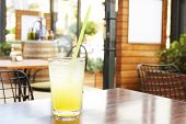 A Glass Of Fresh Ice Cold Lemonade On Wooden Table Of Coffee Shop Patio With Green Bushes On Backgro poster