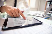 Businessperson Analyzing Invoice On Digital Tablet poster