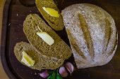 Sliced Fresh Bread With Slices Of Butter And Garlic Cloves poster