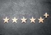 Five Wooden Stars And A Plus, On A Concrete Gray Background. The Concept Of The Highest Evaluation O poster