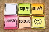 dream, believe, create and succeed concept - handwriting on sticky notes with a smiley against burla poster