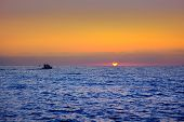 blue sea sunrise with sun in horizon with fishing boat sailing