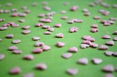Pink Confectionery Sprinkling In The Form Of Hearts On Green Background. Picture For A Menu Or A Con poster