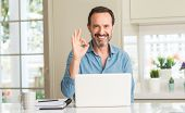 Middle age man using laptop at home doing ok sign with fingers, excellent symbol poster