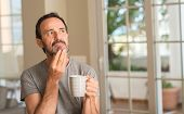 Middle age man drinking coffee in a cup serious face thinking about question, very confused idea poster