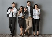 Multicultural Business People In Formal Wear Showing Ok Sign While Standing At Grey Wall poster