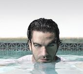 picture of good-looker  - Sexy male model in swimming pool with copy space above - JPG