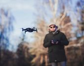 Flying Black Drone On The Background Of A Man. Focus On The Drone poster