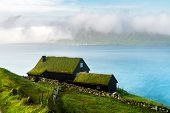 Foggy morning view of a house with grass roof in the Velbastadur village on Streymoy island, Faroe i poster